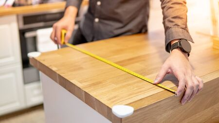 Male hand interior designer using tape measure for measuring size of wooden countertop in modern kitchen showroom in furniture store. Shopping material design for home improvement. Stock Photo - 128366270