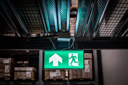 Green emergency exit sign or fire exit sign showing the way to escape with arrow symbol.