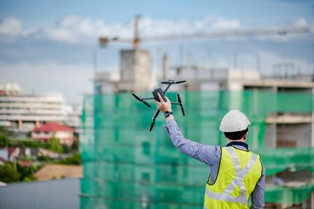Asian engineer man holding drone at construction site. Male worker using unmanned aerial vehicle (UAV) for land and building site survey in civil engineering project.