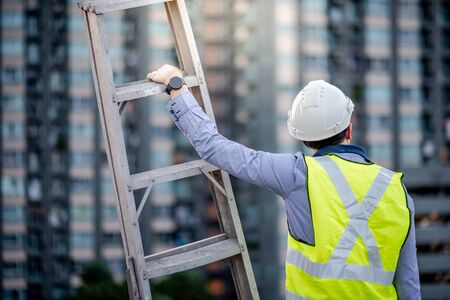Asian maintenance worker man with safety helmet and green vest carrying aluminium step ladder at construction site. Civil engineering, Architecture builder and building service concepts