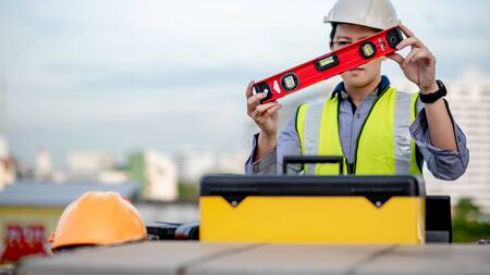 Asian maintenance worker man holding red aluminium spirit level tool or bubble levels over tool box at construction site. Equipment for civil engineering project