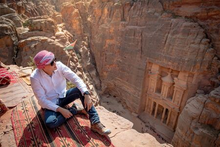 Asian man traveler sitting on carpet viewpoint in Petra ancient city looking at the Treasury or Al-khazneh, famous travel destination of Jordan and one of seven wonders. Imagens