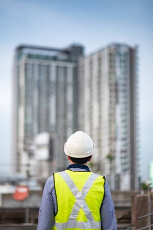 Asian maintenance worker man with safety helmet and green vest standing at construction site. Civil engineering, Architecture builder and building service concepts