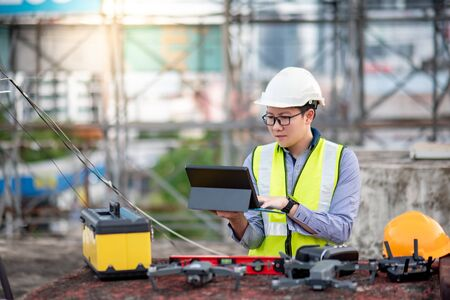 Asian engineer man working with drone, laptop and working tools at construction site. Male worker using unmanned aerial vehicle (UAV) for land and building site survey in civil engineering project. Banco de Imagens