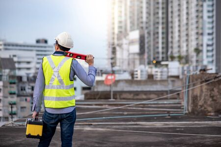 Asian maintenance worker man holding red aluminium spirit level tool or bubble levels and wprking tool box at construction site. Equipment for civil engineering project