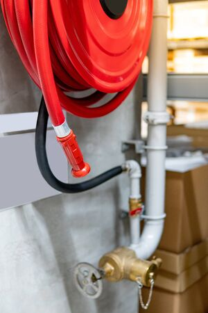 Red fire hose reel and water gate valve for hydrant system. Fire protection equipment in public building. Stock Photo