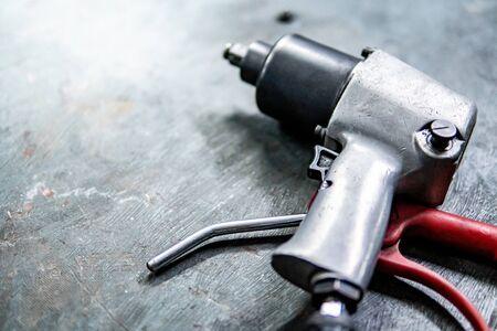 Llave neumática sobre piso de concreto en taller de reparación de automóviles. Concepto de reparación de ruedas de coche