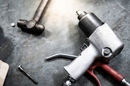 Pneumatic wrench and hammer on concrete floor in auto repair shop. Car wheel repairing concept