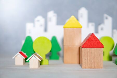 Group of wooden house and tree toy models with blurred city background on the table. Urban living concept Stockfoto