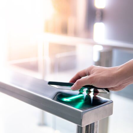 Male hand using smartphone to open automatic gate machine in office building