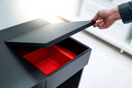 Hand opening black cosmetic table top with the red partition inside. Shopping in furniture store concept