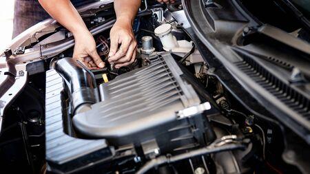 Mano maschio del meccanico che ripara il motore dell'auto nel garage. Concetto di industria automobilistica