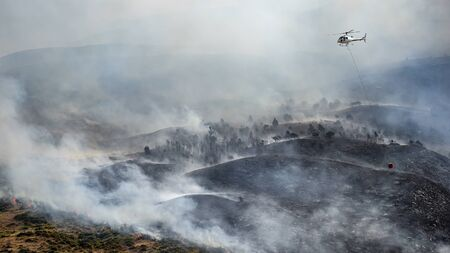 Firefighting helicopter with bucket drop water on forest fire or wildfire.