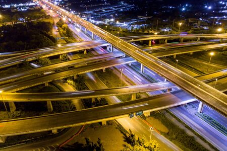 Aerial view of illuminated road interchange or highway intersection with busy urban traffic speeding on the road at night. Junction network of transportation taken by drone.