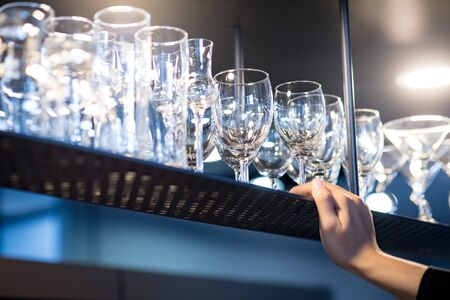 Male hand holding wineglass rack above bar counter in the kitchen. Glassware for drinking wine and beer.