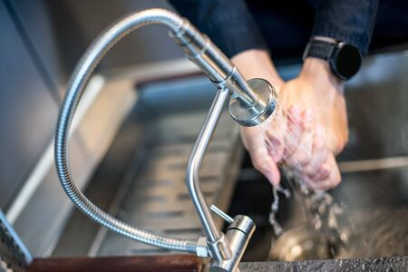 Washing hand in kitchen sink with modern stainless faucet. Saving water concept