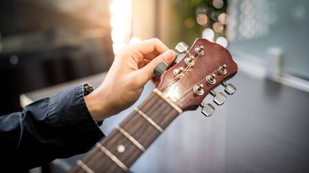 Male hand guitarist adjusting pegs on acoustic guitar during music lesson at home. String musical instrument concept Stok Fotoğraf