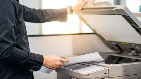 Male businessman using photocopier for copying and printing report paperwork in office. Electronic equipment and supply for business organization.