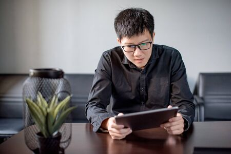 Young Asian businessman using digital tablet in office meeting room. Male entrepreneur reading news on social media app. Online marketing and Big data technology for E-commerce business.  Stock Photo