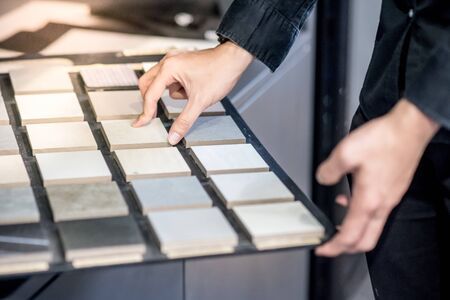 Male architect or interior designer hand choosing ceramic texture sample from swatch board in design studio. Floor and wall finishing material for architecture and construction industry. Banco de Imagens