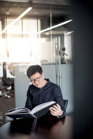 Asian businessman wearing glasses reading book in public library. Education research and self improvement with printed media. World Book Day concept
