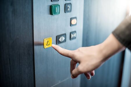 Male forefinger pressing on emergency stop and alarm button in elevator (lift). Mechanical engineering concept Zdjęcie Seryjne