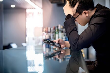 Young Asian man feeling stress, tired and headache while using chat app on smartphone at counter bar. Communication problem on social media mobile application. Cyberbullying concept