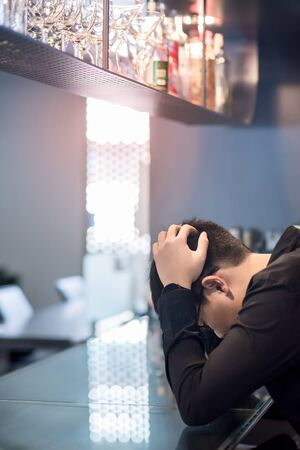 Asian man in black shirt feeling headache and hangover at bar counter in the pub. Mental health illness or depression from life problem. Nightlife in nightclub concept
