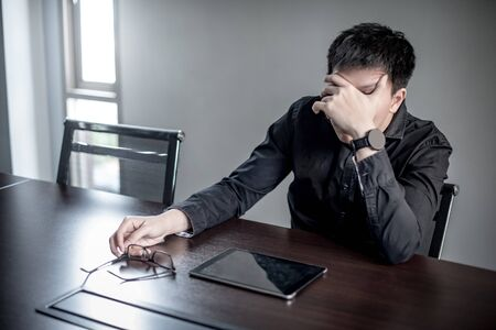 Overworked Asian Businessman feeling stressed, tired and headache sitting with digital tablet in meeting room. Depression from business problem. Mental health illness or office syndrome concept