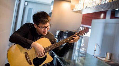 Young Asian man guitarist playing acoustic guitar at bar counter in the cafe. Practicing string musical instrument. Music and entertainment concept.