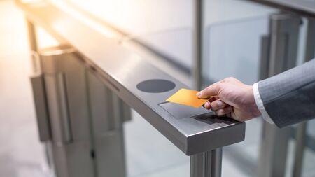 Mano dell'uomo d'affari con abbigliamento da lavoro utilizzando smart card arancione per aprire la macchina automatica del cancello nell'edificio per uffici. Concetto di routine di lavoro