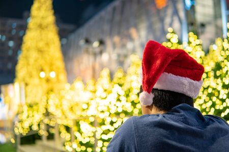Asian man wearing Santa hat looking at illuminated Christmas tree in Xmas holiday and New Year celebration event.