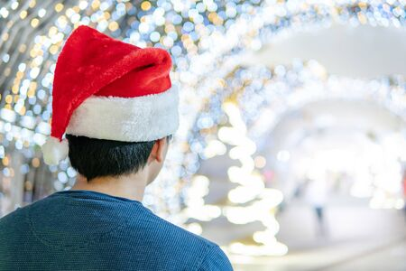 Asian man wearing Santa hat standing in illuminated festive light tunnel. Xmas holiday and New Year celebration event.