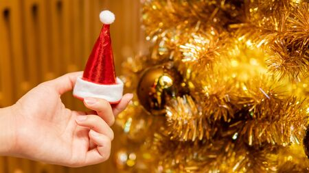 Male hand holding mini santa hat near gold Christmas tree with decorative Christmas dacoration. Xmas and New Year Celebration concept