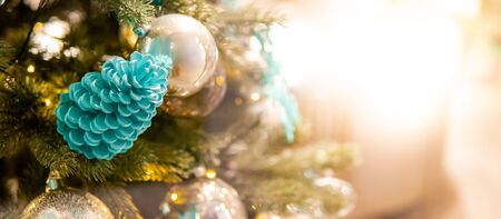 Christmas decoration for festive season. Light blue pine cone and shiny Christmas ball on branch of Christmas tree with bright copy space.