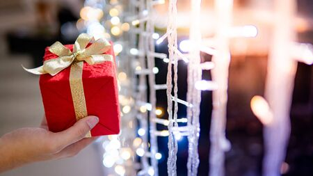 Male hand holding red Christmas gift box or New Year present with blurred illuminated decorative Christmas lights in the background. Decoration for festive season. New Year Celebration concept