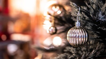 Silver Christmas ball on branch of Christmas tree with red copy space in the background. Decoration for festive season. Xmas and New Year celebration concept