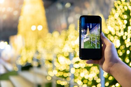 Male hand taking photo of illuminated Christmas tree in Xmas holiday and New Year celebration event from  smartphone. Mobile camera app for festive season concept
