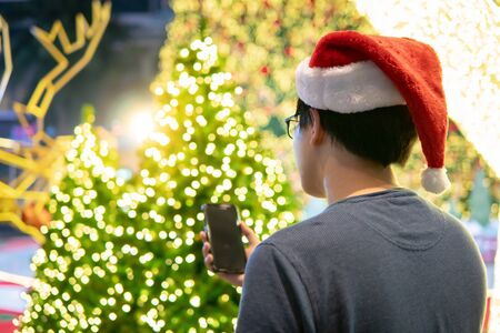 Asian man with Santa hat enjoy using smartphone in Xmas holiday and New Year celebration event. Mobile app for festive season concept