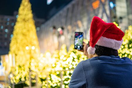 Asian man with Santa hat enjoy taking photo of illuminated Christmas tree in Xmas holiday and New Year celebration event from his smartphone. Mobile camera app for festive season concept Zdjęcie Seryjne