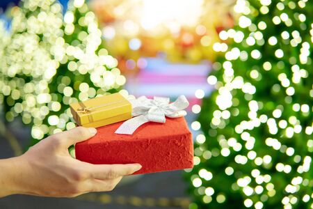 Male hand holding red and gold Christmas gift box or New Year present with blurred illuminated decorative Christmas tree in the background. Decoration for festive season. New Year Celebration concept