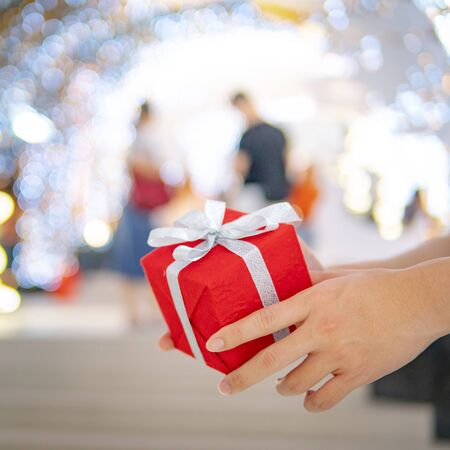 Male hand holding red Christmas gift box or New Year present with blurred illuminated Christmas lights and couple in the background. Decoration for festive season. New Year Celebration concept