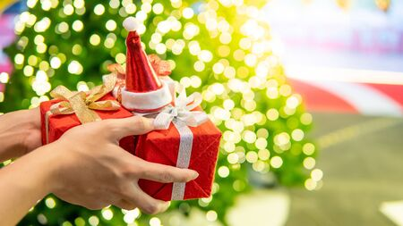 Male hand holding red Christmas gift box or New Year present and mini santa hat with blurred illuminated Christmas lights in the background. Decoration for festive season. New Year Celebration concept