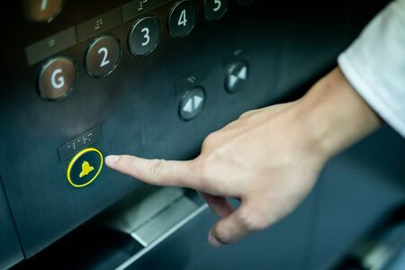Male forefinger pressing on emergency stop and alarm button in elevator (lift). Mechanical engineering concept Imagens
