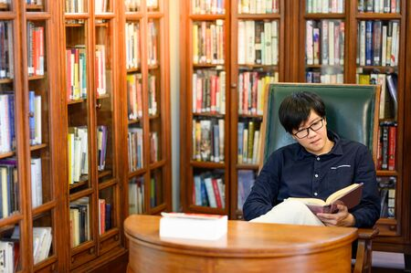 Smart Asian man university student sitting by vintage bookshelf reading book. Textbook resources in college library for educational subject and research. Scholarship for education opportunity. Foto de archivo - 141067338