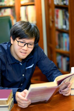 Smart Asian man university student sitting by vintage bookshelf reading book. Textbook resources in college library for educational subject and research. Scholarship for education opportunity. Foto de archivo - 141067729