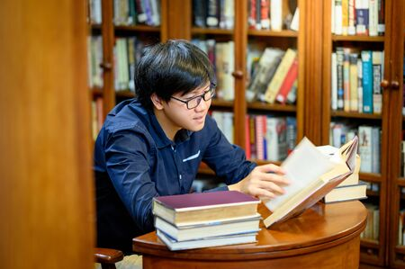 Smart Asian man university student sitting by vintage bookshelf reading book. Textbook resources in college library for educational subject and research. Scholarship for education opportunity. Foto de archivo