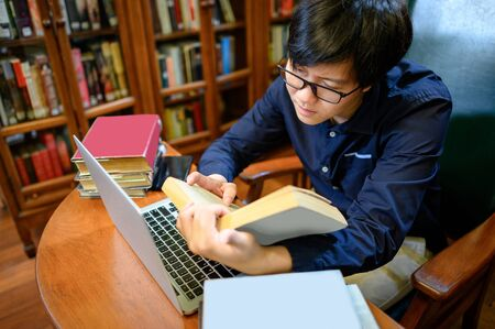 Asian man university reading book and using laptop computer nearby vintage bookcase or bookshelf in college library. Textbook resources for education research. Scholarship opportunity concept