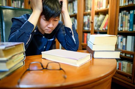 Smart Asian man university student feeling stressed and anxious while reading book by vintage bookshelf in college library for education subject and research. Scholarship for education opportunity. Foto de archivo - 141067351