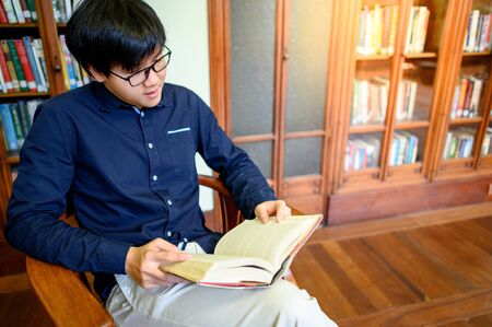 Smart Asian man university student sitting by vintage bookshelf reading book. Textbook resources in college library for educational subject and research. Scholarship for education opportunity. Foto de archivo - 141067715